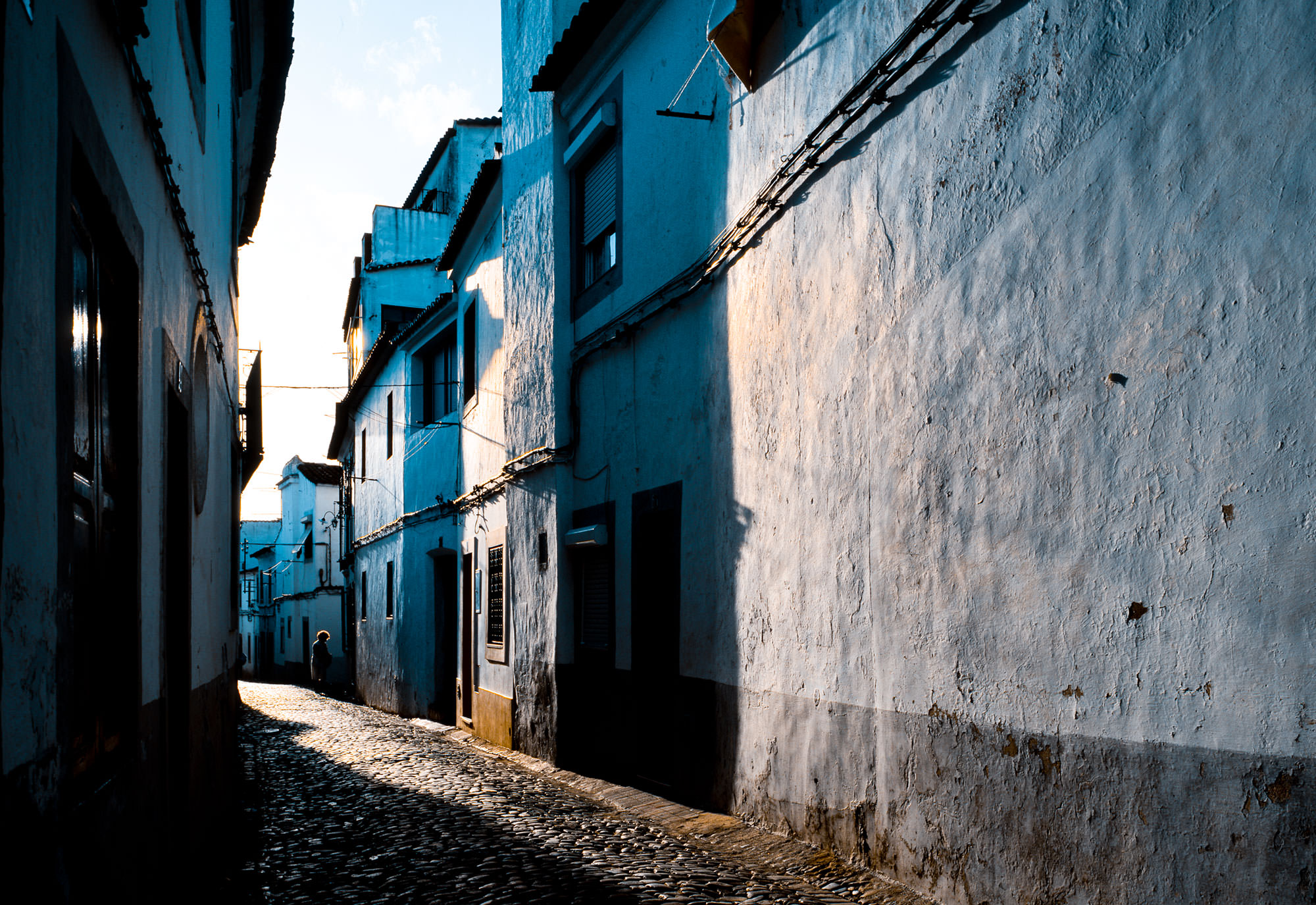 Photograph of Evora, Portugal in the early morning.  An old cobblestone alley.