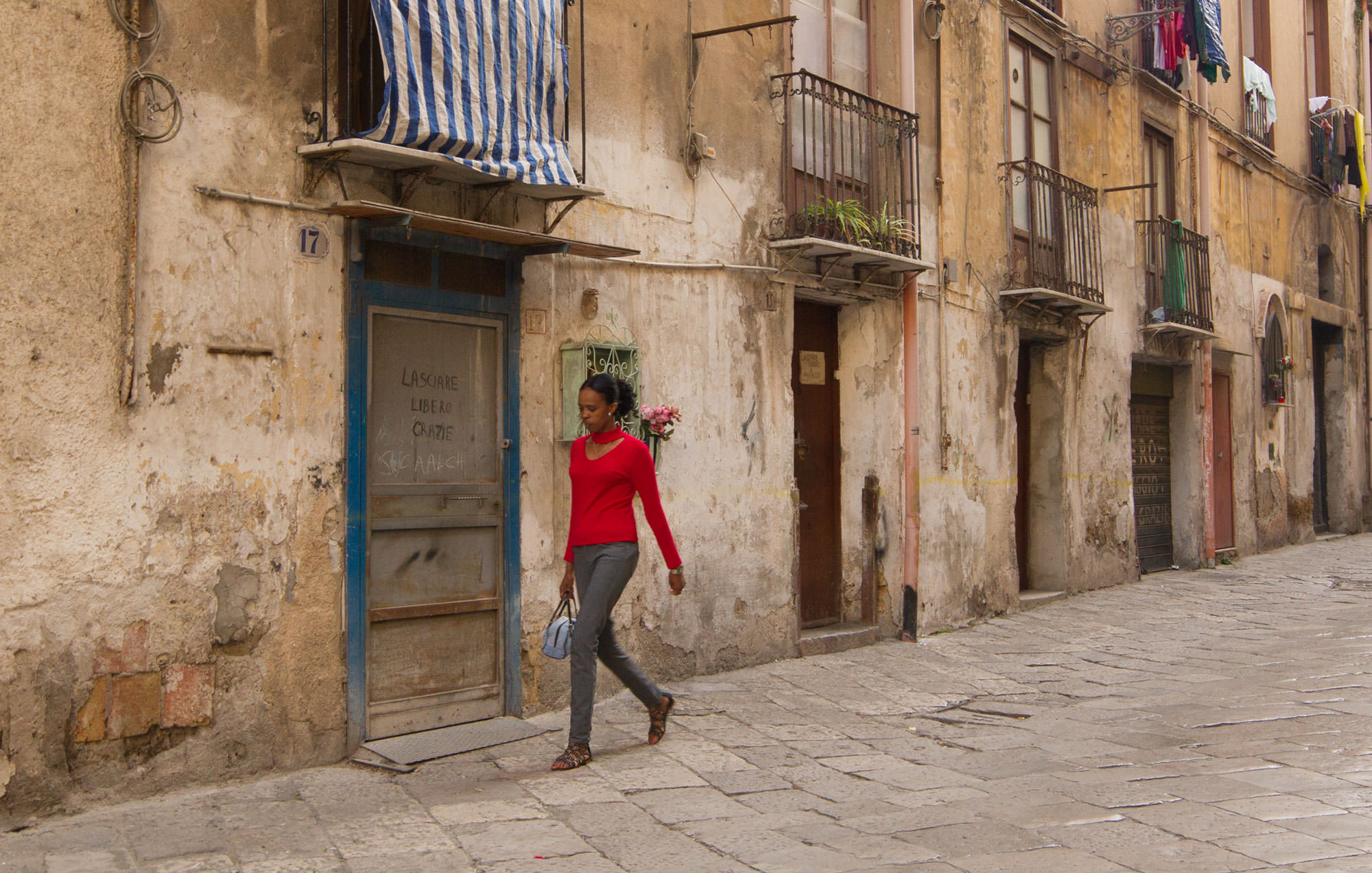 A woman walks in the Kalsa District of Palermo, Sicily.