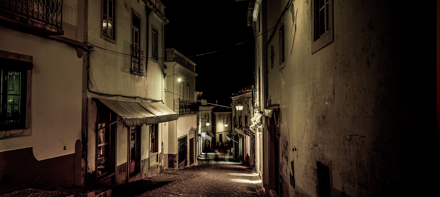 Photo of Evora, Portugal at Night.  Sloped alleyways.